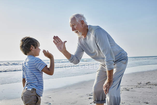 Grandfather and grandson high fiving — Stock Photo