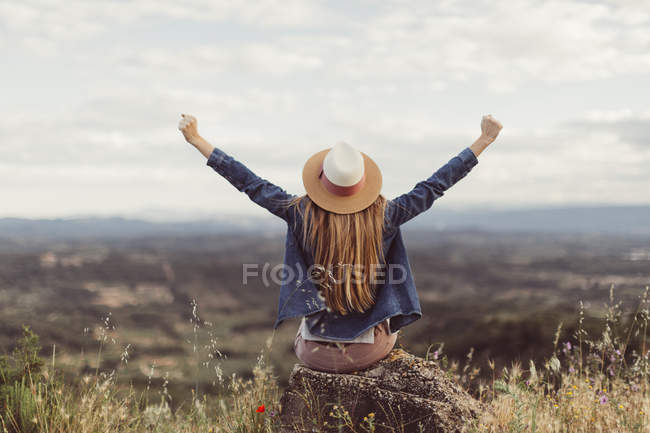 Woman sitting on rock with hands raised — Stock Photo