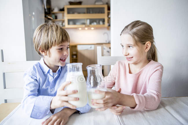 Brother and sister clinking glasses — Stock Photo
