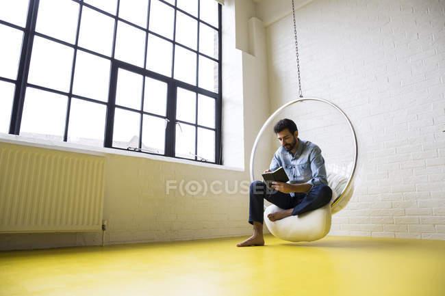 Homme lisant le livre sur la chaise d'oscillation — Photo de stock