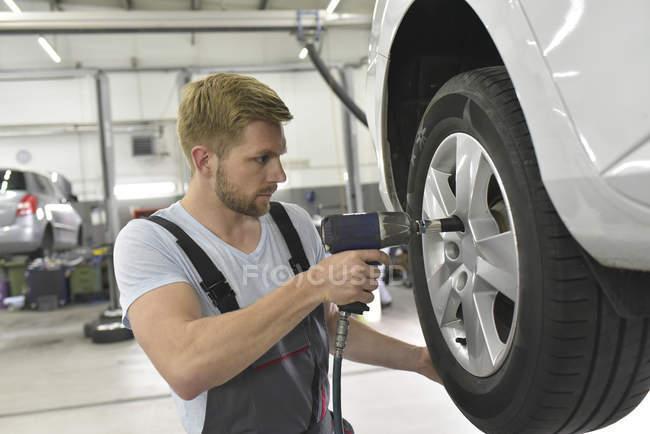Mechanic changing car tyre — Stock Photo