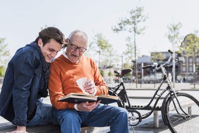 Senior homme et petit-fils regardant album photo — Photo de stock