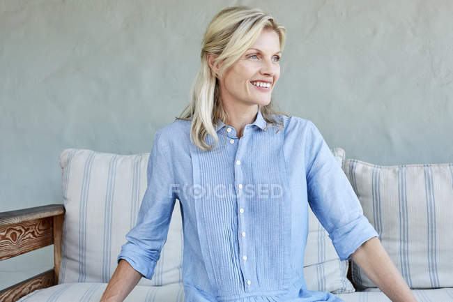 Жінка сидить на дивані. — стокове фото