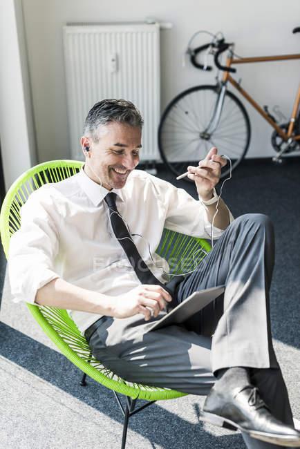 Empresário sentado em poltrona com tablet — Fotografia de Stock