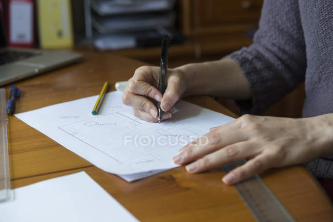Close-up of woman drafting ground plan at desk — Stock Photo