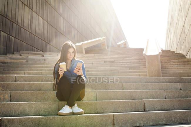 Donna seduta sulle scale con il caffè per andare — Foto stock