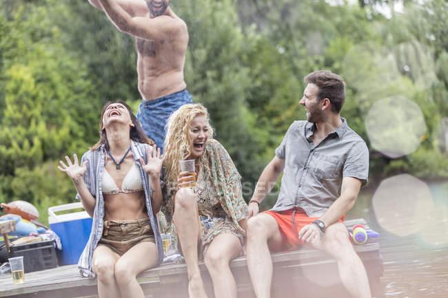 Glückliche Freunde, die Spaß auf einem Steg am See — Stockfoto