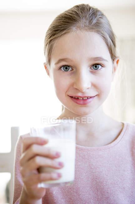 Ragazza sorridente che tiene un bicchiere di latte — Foto stock