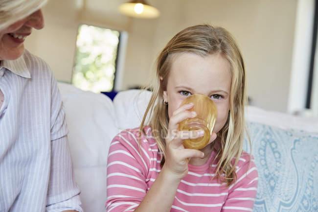 Маленька дівчинка питної Сік з бабуся — стокове фото