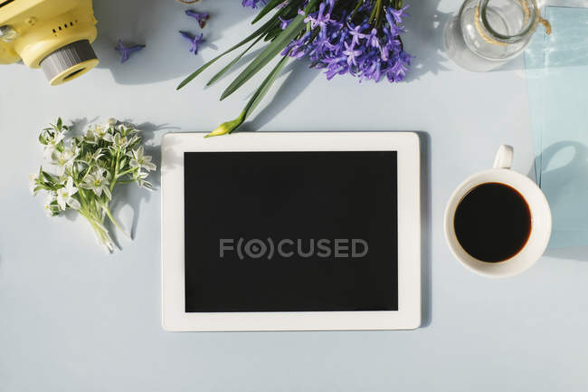 Tablet with cup of coffee and flowers — Stock Photo