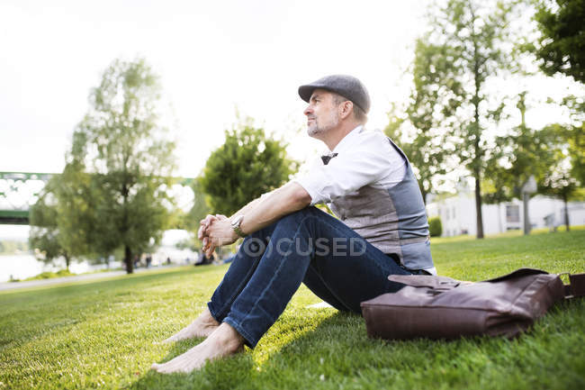 Businessman sitting on grass — Stock Photo