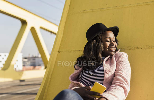 Жінка сидить на мосту з смартфон — стокове фото