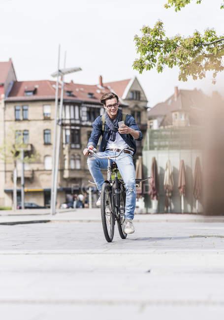 Людина, їзда на велосипеді і використання телефону — стокове фото