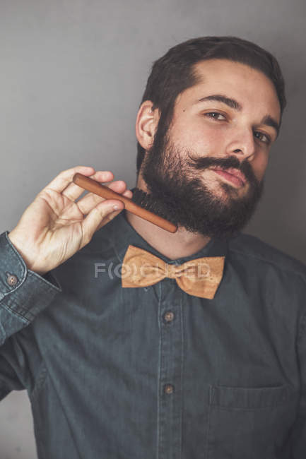 Man combing beard with wooden brush — Stock Photo