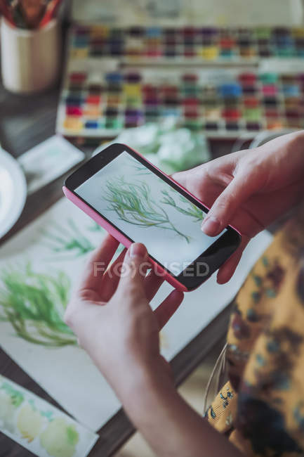 Woman taking pictures of painted plants — Stock Photo