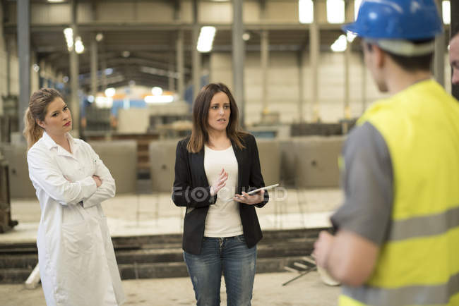 Boss briefing coworkers in factory — Stock Photo