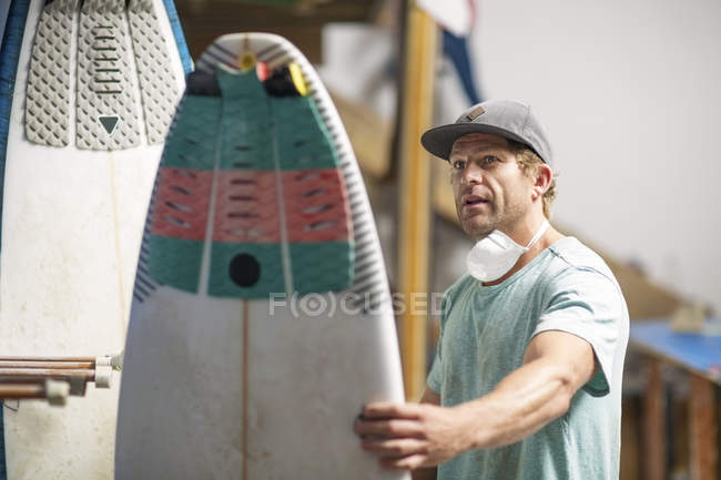 Surfshop employee admiring surfboard — Stock Photo