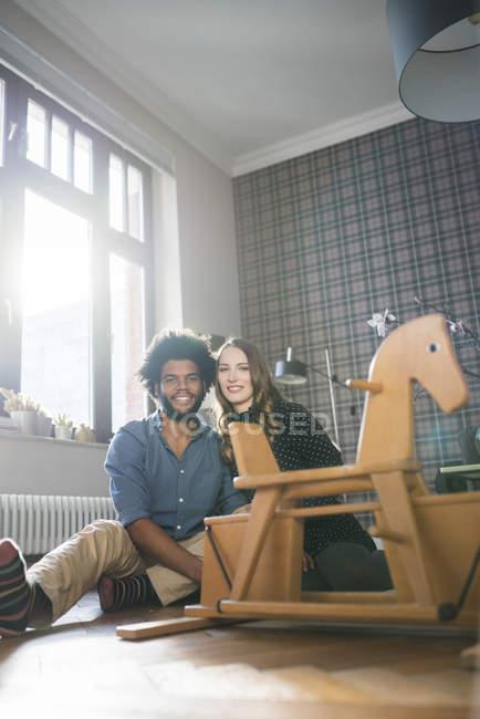 Пара, сидячи на підлогу перед іграшковий кінь-качалка — стокове фото
