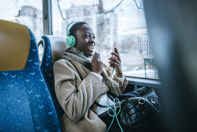 Young woman using headphones in a bus — Stock Photo
