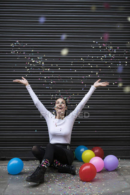 Woman on pavement with balloons — Stock Photo