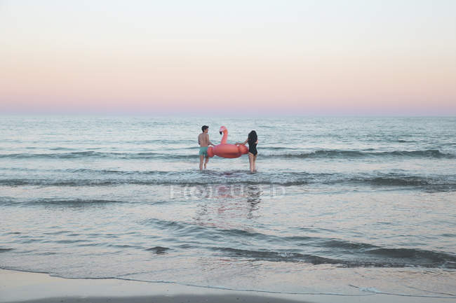 Couple walking in sea with inflatable flamingo — Stock Photo
