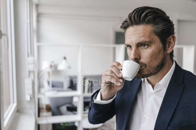 Businessman sipping from cup — Stock Photo