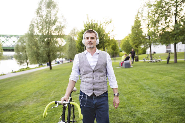 Бізнесмен з велосипеда і навушники — стокове фото