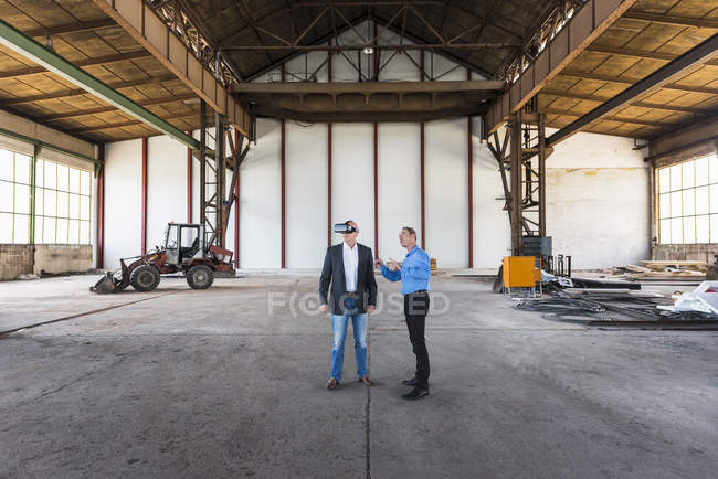 Businessmen interacting in old industrial hall — Stock Photo