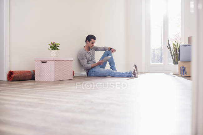 Young man in new home sitting on floor with tablet — Stock Photo