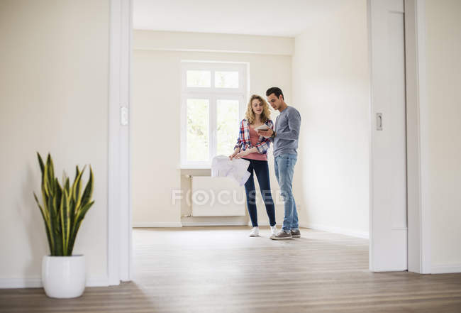 Young couple in new home with tablet and ground plan — Stock Photo