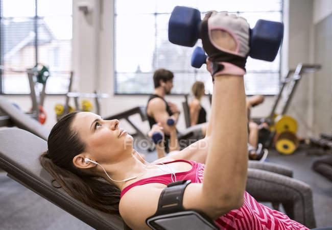Женщина упражняется с гантелями в тренажерном зале — стоковое фото