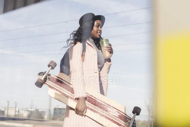 Woman carrying skateboard — Stock Photo