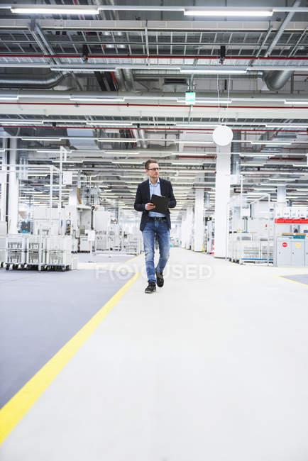 Man walking in factory shop floor — Stock Photo
