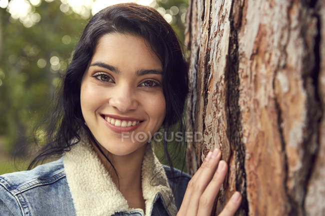 Young woman leaning on tree trunk — Stock Photo