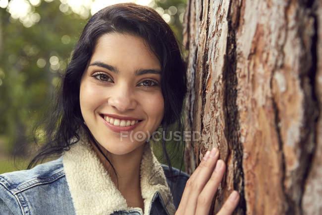 Молода жінка, спираючись на стовбур дерева — стокове фото