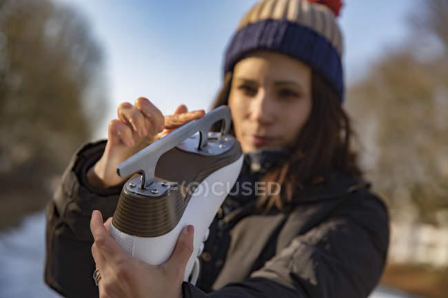 Donna che esamina la lama del pattino ghiaccio — Foto stock