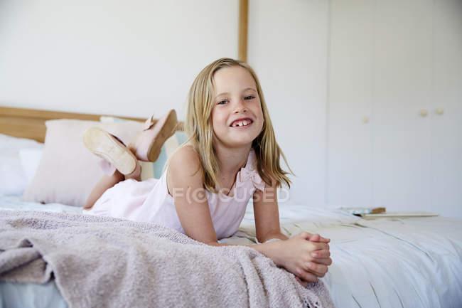Little girl lying on bed — Stock Photo