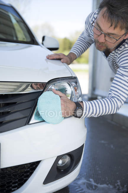 Man cleaning headlight of his car — Stock Photo