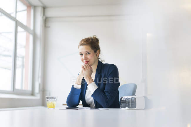 Businesswoman sitting at desk — Stock Photo