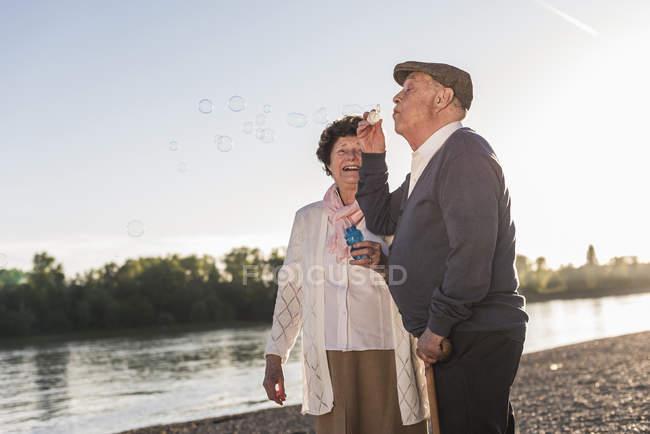 Старший чоловік дме мильних бульбашок — стокове фото