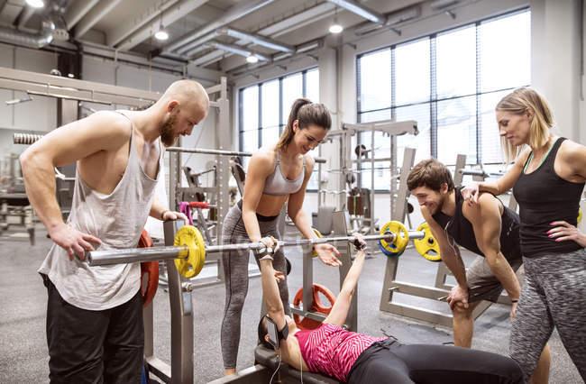 Personas en gimnasio entrenamiento levantamiento de pesas - foto de stock