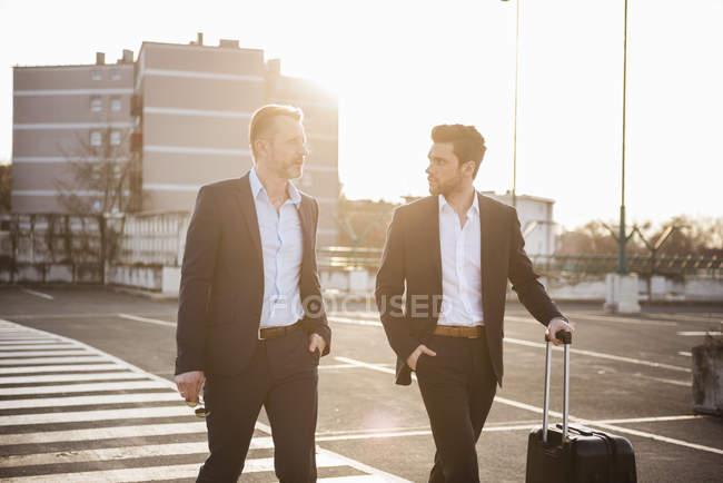 Businessmen walking at parking place — Stock Photo