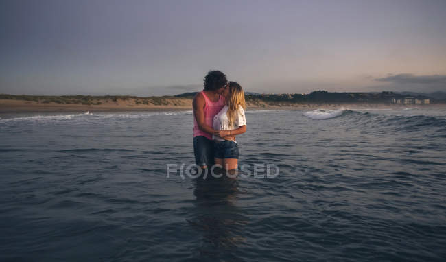Young couple kissing in sea at dusk — Stock Photo