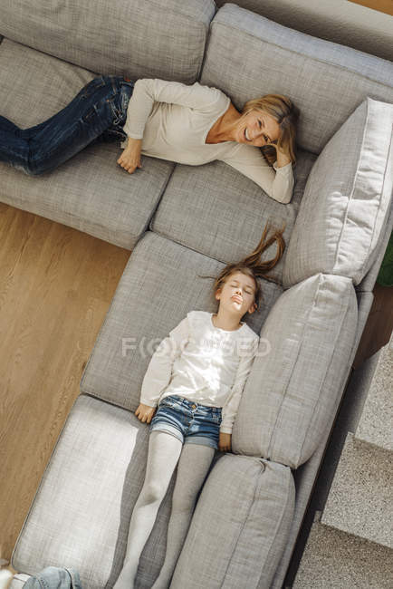 Femme et fille couché sur le canapé — Photo de stock
