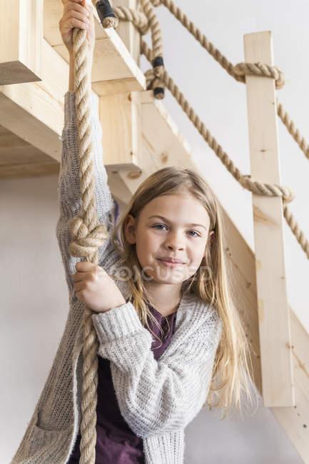 Girl hanging on climbing rope — Stock Photo