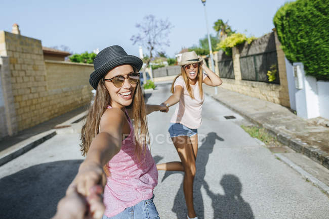 Друзі, тримаючись за руки на вулиці — стокове фото