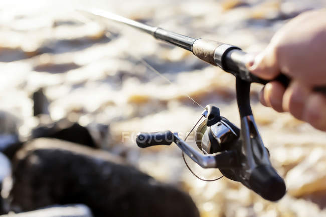 Close up of Hand holding fishing rod — Stock Photo