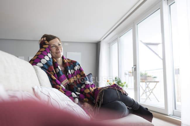 Femme sur canapé enveloppé dans une couverture — Photo de stock