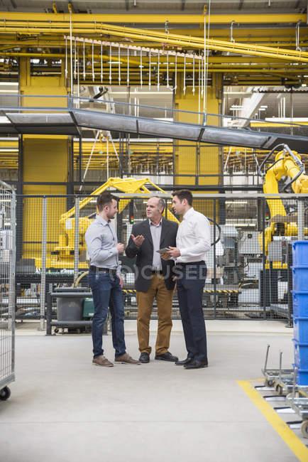 Мужчины разговаривают на фабрике — стоковое фото