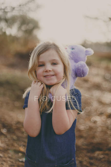 Smiling girl with teddy — Stock Photo